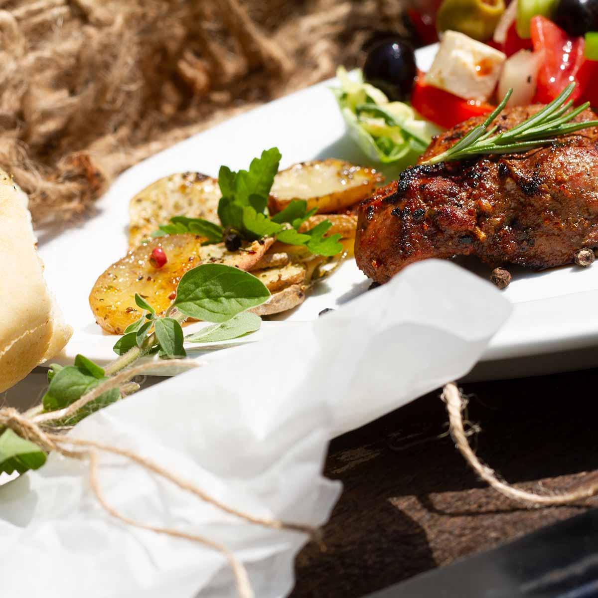 Gegrilltes Fleisch mit Kartoffeln und Salat auf Teller serviert