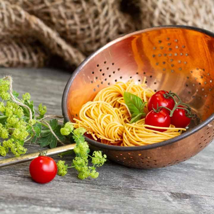 Paste mit Tomaten in einem Sieb und auf altem Holztisch serviert